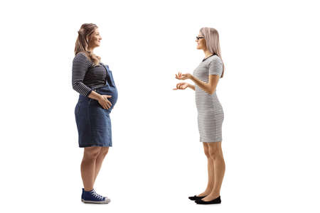 Full length profile shot of a blond woman talking to her pregnant friend isolated on white background