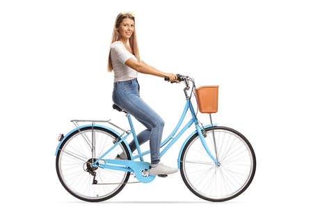 Young female with long hair riding a bicycle and smiling at camera isolated on white background