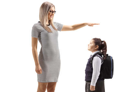 Young woman gesturing with hand and showing the height of a schoolgirl isolated on white background