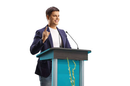 Man speaker with a hands free microphone on a pedestal gesturing with finger isolated on white background Фото со стока