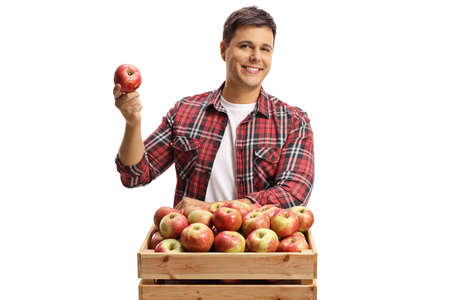 Young man posing with a wooden crate full of fresh organic apples isolated on white background Reklamní fotografie