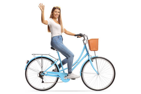 Young female with long hair riding a bicycle and waving isolated on white background Reklamní fotografie