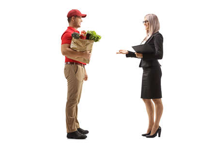Full length profile shot of a man delivering a bag of groceries to a businesswoman isolated on white background