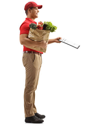 Full length profile shot of a man delivering groceries and holding a clipboard isolated on white background