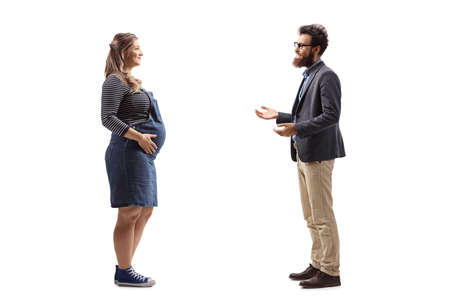 Full length profile shot of a pregnant woman and a bearded man having a conversation isolated on white background Reklamní fotografie