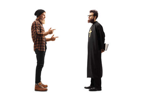 Full length profile shot of a young bearded guy talking to a priest with a bible isolated on white background