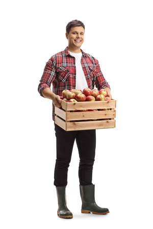 Full length portrait of a farmer holding a wooden crate full of fresh organic apples isolated on white background