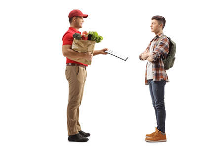 Full length profile shot of a man delivering groceries and giving a document to a young male student isolated on white background Reklamní fotografie