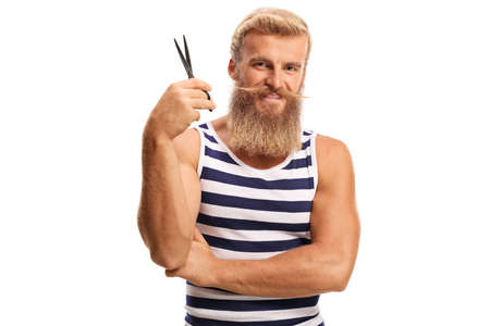 Bearded guy holding a pair od scissors and smiling isolated on a white background