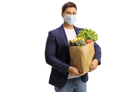 Young man with a grocery bag wearing a protective face mask isolated on white background