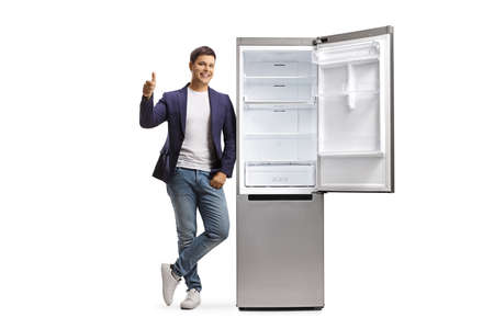 Full length portrait of a young man in jeans and suit leaning on an empty open fridge and showing thumbs up isolated on white background Reklamní fotografie