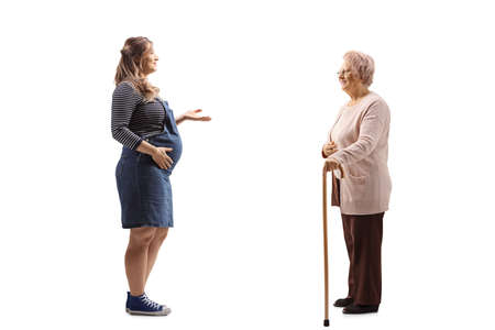 Full length profile shot of a pregnant woman gesturing and talking to an elderly woman with a walking cane isolated on white background Reklamní fotografie