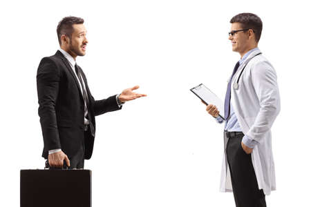 Businessman with a briefcase talking to a doctor isolated on white background Reklamní fotografie