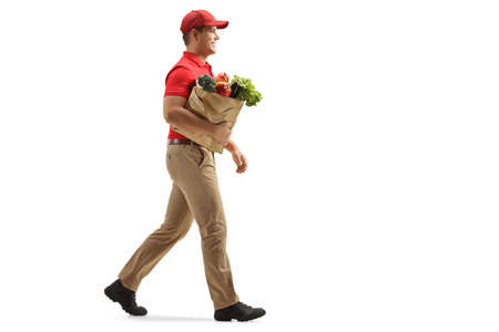 Full length profile shot of a delivery man walking with a bag of groceries isolated on white background