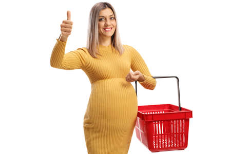 Smiling pregnant woman holding a shopping basket and showing thumbs up isolated on white background