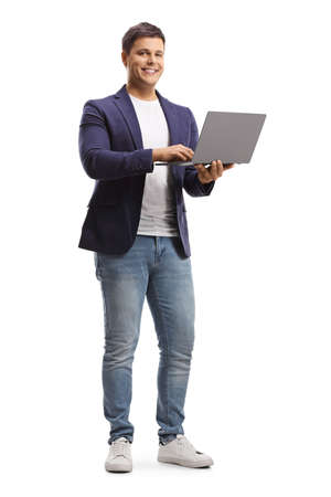 Full length portrait of a young man holding an open laptop computer and smiling at camera isolated on white background