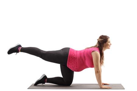 Pregnant woman kneeling and exercising on a mat isolated on white background Reklamní fotografie