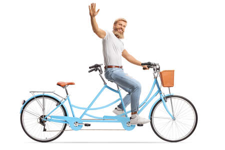 Smiling bearded man riding a tandem bicycle alone and waving isolated on white background
