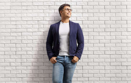 Smiling young man in jeans and suit leaning on a white brick wall and looking up isolated on white background