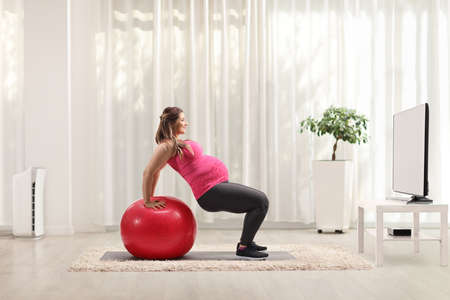 Woman doing pregnancy exercises at home with a fitness ball in front of a tv Reklamní fotografie