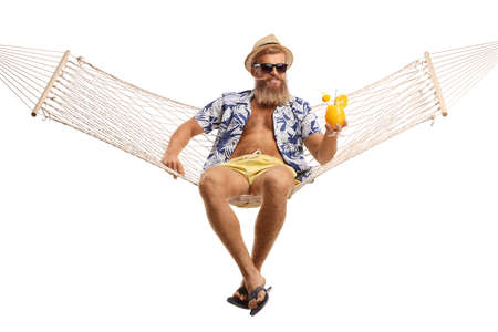 Young bearded man with hat and sunglasses sitting on a hammock swing with a cocktail isolated on white background