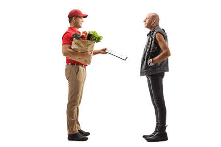 Full length profile shot of a man delivering groceries in a paper bag to a punk isolated on white background