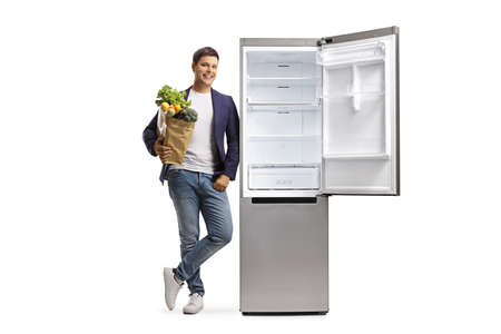 Full length portrait of a young man holding a grocery bag and leaning on a fridge isolated on white background Reklamní fotografie
