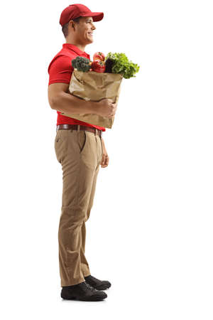 Full length profile shot of a delivery man holding groceries in a paper bag isolated on white background