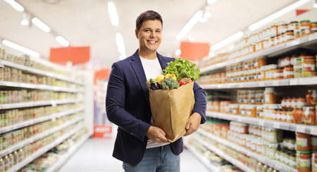 Young man with a grocery bag standing in a supermarket and smiling