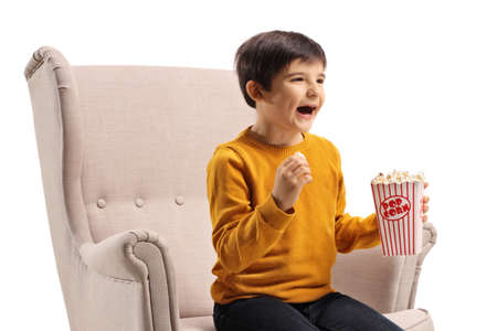 Child sitting in an armchair with popcorn and laughing isolated on white background