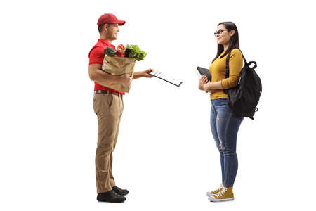 Full length profile shot of a delivery man holding groceries in a paper bag and giving a document to a female student isolated on white background