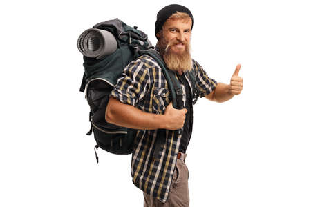 Bearded man hiker with a backpack smiling and showing thumbs up isolated on white background Reklamní fotografie