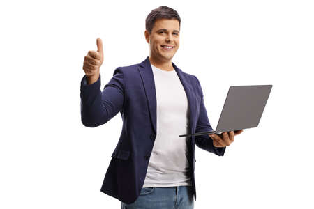 Cheerful young man holding an open laptop computer and showing thumbs up isolated on white background