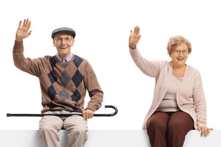 Elderly couple sitting on a blank billboard sign and waving at the camera isolated on white background