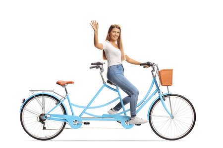Young woman in casual clothes riding a tandem bicycle and waving isolated on white background