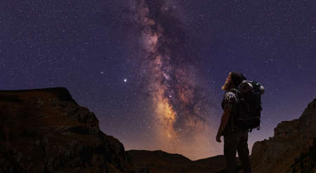 Hiker looking at a mountain range with stars and the milky way on night sky
