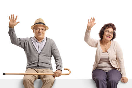 Elderly man and woman sitting on a blank billboard sign and waving at the camera isolated on white background