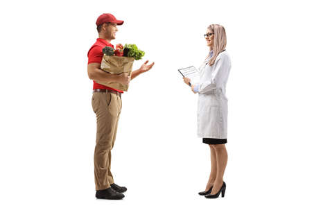Full length profile shot of a delivery man holding groceries in a paper bag and talking to a female doctor isolated on white background 免版税图像