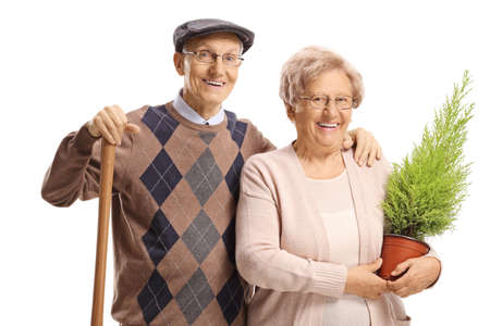Happy elderly couple with a plant and a shovel isolated on white background Reklamní fotografie