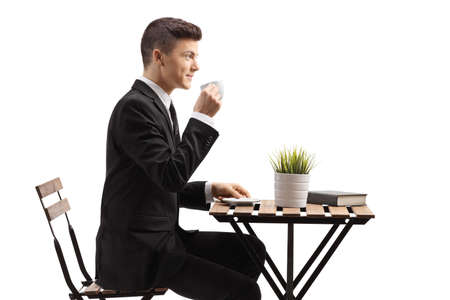 Young businessman in a suit sitting and drinking coffee isolated on white background