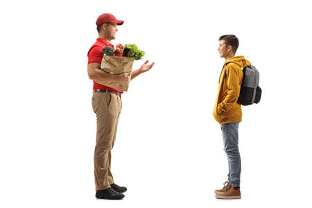 Full length profile shot of a delivery man holding groceries in a paper bag and talking to a teenage schoolboy isolated on white background