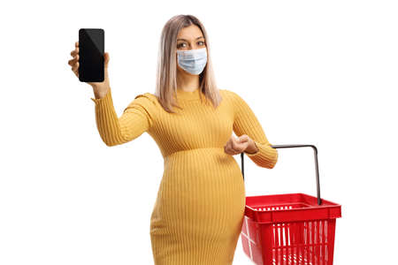 Pregnant woman with a protective face mask holding a shopping basket and showing a smartphone isolated on white background