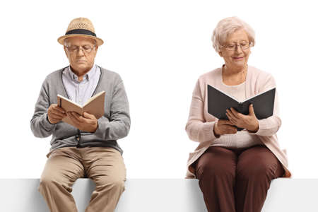 Elderly man and woman sitting on a white panel reading books isolated on white background
