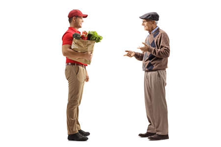 Full length profile shot of a delivery man holding groceries in a paper bag and listening to an elderly male customer isolated on white background