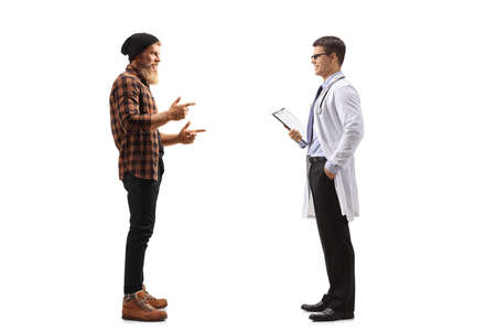 Full length profile shot of a bearded guy standing and talking to a male doctor isolated on white background
