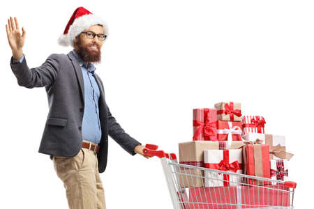 Bearded man with a santa hat waving and walking with a shopping cart full of presents isolated on white background