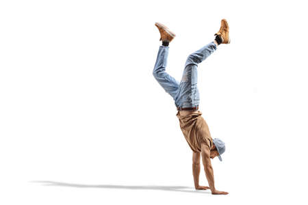 Guy in jeans performing a hand stand isolated on white background Reklamní fotografie