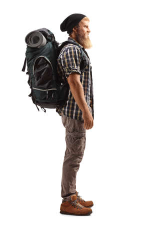 Full length profile shot of a bearded guy hiker with a backpack isolated on white background
