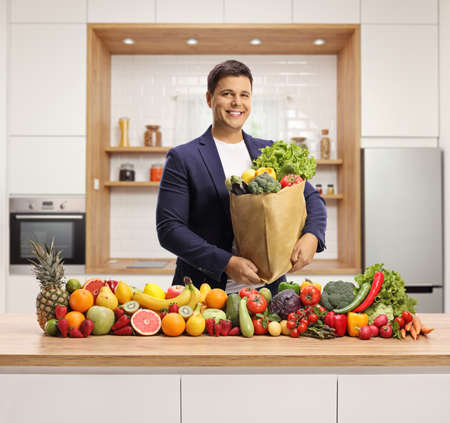 Happy young man with a grocery bag posing in a kitchen with a pile of fresh fruits and vegetables