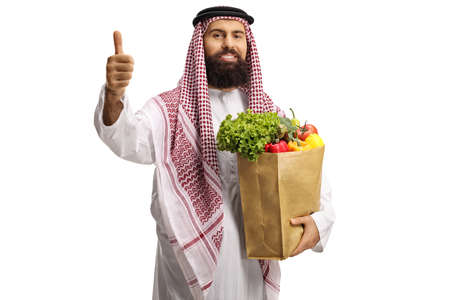 Arab man with a grocery bag standing and showing thumbs up isolated on white background